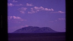 1972: a large mountain ridge amid flatlands under a cloudy blue sky IDAHO Stock Footage