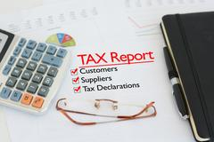Tax report on a desk with tick against customers, suppliers and tax declarations Stock Photos