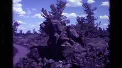 1972: a large craggy gray rock formation sits in a field IDAHO Stock Footage