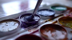 Closeup box of diffirents colors paint. Brush dipped in paint. Artist, stutent Stock Footage