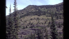1972: panoramic view of a mountain range with forest HOLLAND LAKE MONTANA Stock Footage