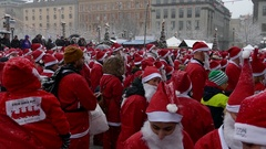 Crowd of Santa Clauses standing clapping under heavy snow for new year charity Stock Footage