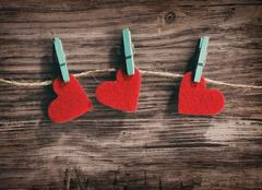 Three red hearts hanging on a cord on a wooden background Stock Photos