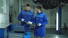 Two auto mechanic in blue uniform preparing the car for full diagnostics Stock Footage