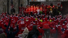 Crowd of Santa Clauses raising their hands together in a gathering for new year Stock Footage