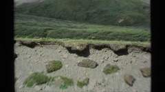 1977: intermittent water erosion has gouged a ravine in a hilly, grassy area Stock Footage