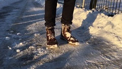 Mans hitting his foot on snow Stock Footage