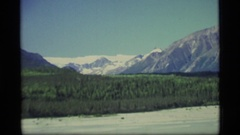 1977: a zoom out from a treeline and mountains reveals a large frozen expanse. Stock Footage