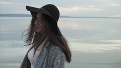 Young woman in black hat and glasses near the sea at sunset Stock Footage