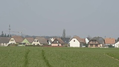 Green agricultural field with beautiful French village houses Stock Footage