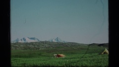 1977: a person doing warmup near tent, pitched near snowy mountains ALASKA Stock Footage