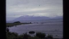 1977: a long rocky mountain range sits behind a large lake ALASKA Stock Footage