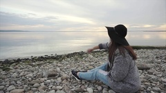 Young woman sitting on pebble beach throwing stones into the water Stock Footage
