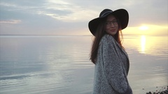 Young pretty woman in black hat and glasses near the sea at sunset Stock Footage