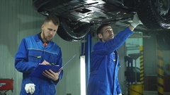 Young workshop employees working together underneath a lifted car Stock Footage