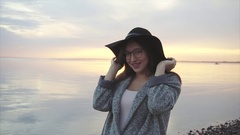 Young pretty and smiling woman in black hat and glasses near the sea at sunset Stock Footage