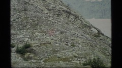 1977: rocky slope with ice fields and exposed rocks and snow in the background Stock Footage