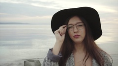 Young pretty woman in black hat and glasses eye wink near the sea at sunset Stock Footage