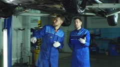 Male mechanics using digital tablet while working under lifted car at auto Stock Footage