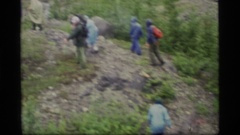1977: several backpackers walking up a rocky knob and clip of an adjacent peak Stock Footage