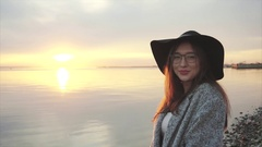 Young pretty smiling woman in black hat and glasses near the sea at sunset Stock Footage