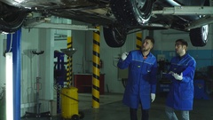 Auto mechanics working underneath a lifted car Stock Footage