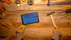 Craftsman remove his working gloves and work with digital tablet. Top view. Stock Footage