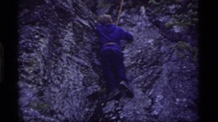 1977: a young boy in hiking shoes moving on his first climbing lesson on a Stock Footage