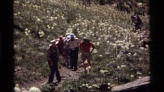 1977: a group of people walk in a single file line up a hill SAPPHIRE LAKE Stock Footage