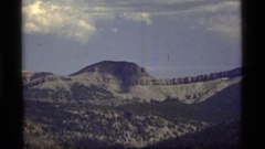 1977: a mountain peak rises above surrounding mountains and juts into a blue sky Stock Footage