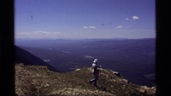1977: four people walk and sit on the top of a cliff edge SAPPHIRE LAKE MONTANA Stock Footage