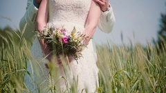 Close-up of beautiful wedding bouquet in hands of a bride standing with her Stock Footage