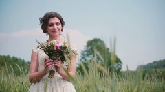 A beautiful young bride looking at her wedding bouquet standing in a wheat field Stock Footage