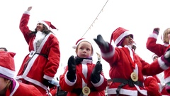 Crowd of Santa Clauses kids dancing crazy together under heavy snow for new year Stock Footage