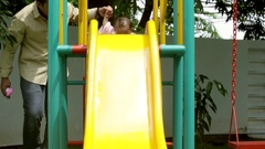 Cute girl playing on slide with dad Stock Footage