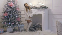 Beautiful sexy brunette woman singing near the Christmas tree at home. New Year Stock Footage