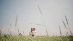 Loving couple standing close to each other in wheat field on their wedding day Stock Footage