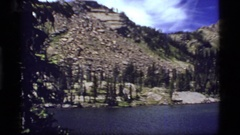 1977: high mountain lake surrounded by rocky exposed hills and some trees Stock Footage