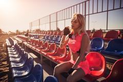 Attractive female runner seated on the beach resting after intensive volleyball Stock Photos