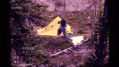 1977: man camping steps out of tent to get dressed. SAPPHIRE LAKE MONTANA Stock Footage