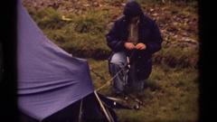 1977: a man tying down a tarp SAPPHIRE LAKE MONTANA Stock Footage