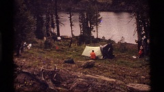1977: a man pitches his tent at a campsite in the woods SAPPHIRE LAKE MONTANA Stock Footage