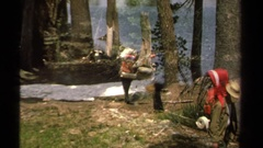 1978: hikers with large backpacks walk among trees by lake  Stock Footage