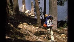 1978: hikers carrying backpacks hike on a forest trail near the bank of a lake Stock Footage