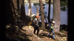 1978: four backpackers walking on a trail in a forest by a lake LAKE TAHOE Stock Footage
