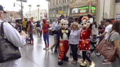 Mickey Mouse and Minnie posing with tourist lady picture Walk of Fame Hollywood Stock Footage