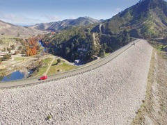 Aerial of vintage car driving over a dam in california Stock Footage
