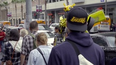 Yellow Transformer costume on crowded Hollywood Boulevard Walk of Fame LA Stock Footage