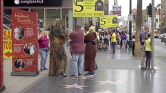 Chewbacca and Yoda costumes on Hollywood Boulevard Walk of Fame taking picture Stock Footage