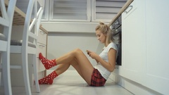 Young blonde woman sitting in a kitchen floor and typing on mobile phone. Stock Footage